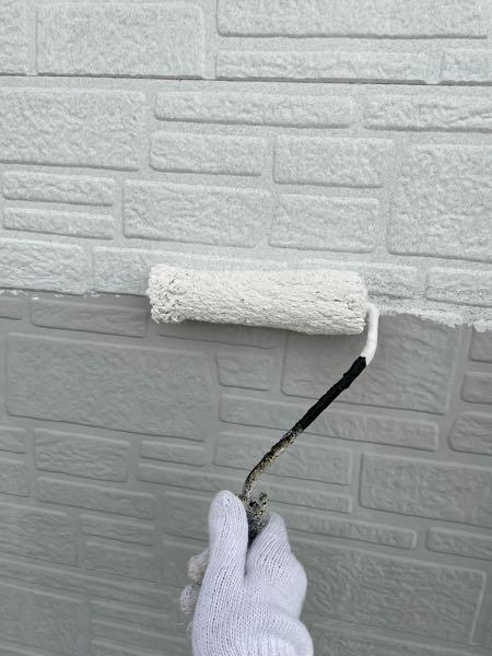 外壁をシーラーで下塗りしています。