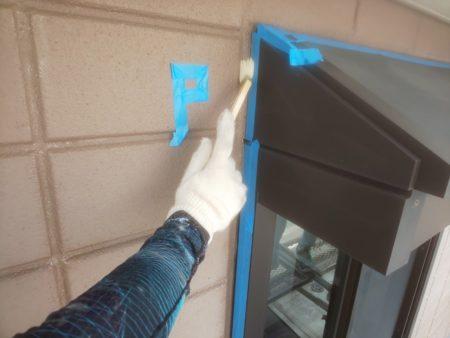 マスキングテープを貼り、コーキングとの接着を高めるプライマ ーを塗っています。
